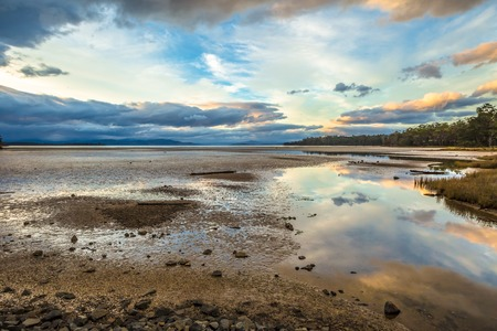 daniels: Daniels Bay at sunset, Lunawanna, Bruny Island, Tasmania, Australia. Clouds in the sky reflected on the water. Stock Photo