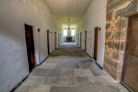 flanked: Port Arthur Historic Site, Tasmania, Australia - January 15, 2015: Corridors of the Separate Prison.  each of the four wings comprised a central corridor flanked by rows of solitary confinement cells.