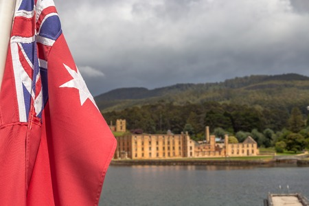 penal: Closeup of the Australian flag and views from the boat to Port Arthur Historic Site Stock Photo