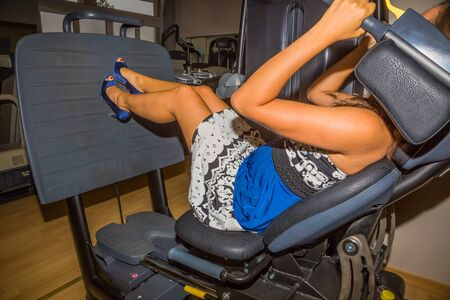 gym dress: Attractive young woman with heels and evening dress in blue and white, training in the gym on a bench press.