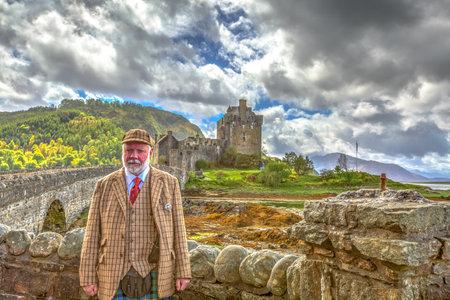 guia turistico: Dornie, Kyle of Lochalsh, Escocia, Reino Unido - 28 may, 2015: La gu�a tur�stica en el vestido tradicional escocesa en frente de la entrada del famoso castillo de Eilean Donan en un d�a nublado