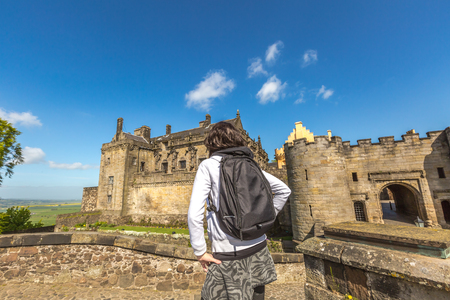 observes: Young tourist woman observes the famous Stirling Castle, in Stirling town, Central Scotland, UK, Europe on a sunny day. Stock Photo