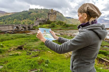 kyle: Young tourist looks at the brochure of Eilean Donan Castle situated on an island at the confluence of three sea lochs. In background the famous Castle, Dornie, Kyle of Lochalsh, Scotland, UK. Stock Photo
