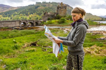 kyle: Young woman tourist looks at a road map. In background the famous and spectacular Eilean Donan Castle in Dornie, Kyle of Lochalsh, Scotland, United Kingdom. Stock Photo