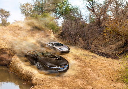 Car race on dirty road between two sport super cars