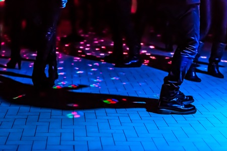 dance club: defocused of a dance floor in a disco club with people dancing under the disco ball blue lights Stock Photo