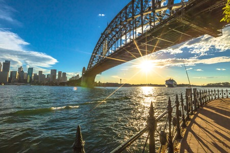 sydney: Sydney, Australia - December 29, 2014:Walking on the path that leads beneath the Sydney Harbour Bridge. City skyline, Cruise and australian flag behind at sunset. Editorial