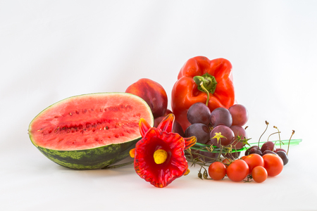 grouping: Group of red fruits and vegetables with glass flower, isolated on white background. Stock Photo
