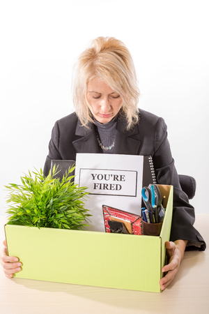 belongings: Fired corporate employee holding her belongings in a cardboard box on the desk and dismissal notification. White background, isolated. Stock Photo