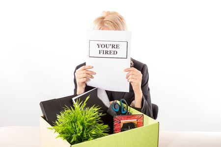 dismissal: Fired corporate employee holding a dismissal notification on her face with her belongings in a cardboard box on the desk. White background, isolated.