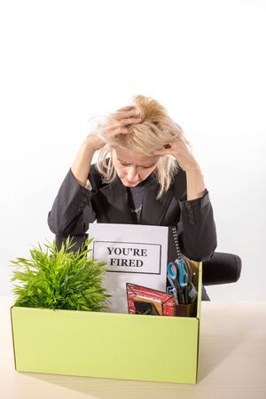 desperation: Fired corporate employee holding her head in desperation with her box on the desk and dismissal notification. White backgroung, isolated. Stock Photo
