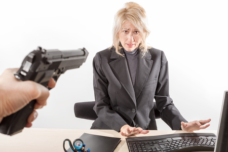 Employee on the menace of a gun during a bank robbery, white background, isolated. Stock Photo