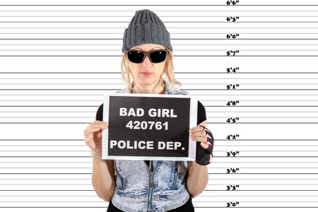 arrested criminal: Arrested Woman posing for a mugshot, holds a signboard with bad girl notice and police department, Pure white background. Stock Photo