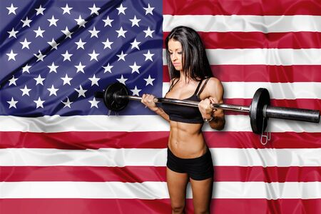 muscularity: Woman bodybuilder lifting straight bar dumbbell on american flag.