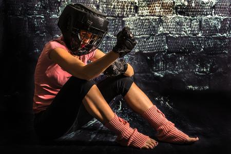 venganza: Combatiente de la mujer meditando en un partido perdido, sentado en el suelo y mirando a los puños, lo siento, pero determinados para la venganza. Concepto de la vulnerabilidad y la feminidad con la fuerza y ??la fuerza de voluntad.