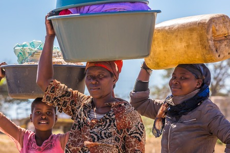 UMkhuze Game Reserve, South Africa - August 24, 2014: African women go to wash their clothes in the river, carrying basins on their heads Éditoriale