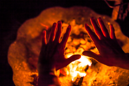 Close-up of a night scene of homeless hands get warm by the fire. Concept of poverty, human warmth, hands that help, hard life, urban life.