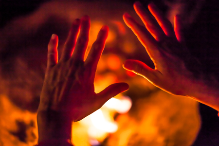 to get warm: Close-up of a night scene of hands get warm by the fire. Concept of poverty, human warmth, camping, bbq, barbeque, braai grill.