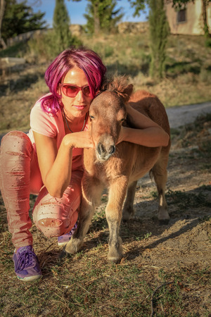 outdoor living: Young and smiling woman enjoying a little pony in a sunny country farm in summer. Concept of outdoor living, healthy life, love for animals. Stock Photo