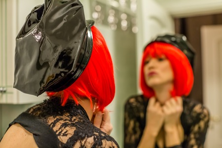 femininity: Transexual with red wig and hat cop in the mirror. Concept of femininity, soul, look inside.