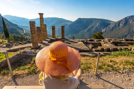 contemplates: A young tourist with a orange wide-brimmed hat contemplates the columns of the Temple of Apollo in the Archaeological Site of Delphi, Central Greece.