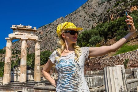 archaeological site: Self shot selfie of a smiling young woman in front of the ruins of the Tholos at the sanctuary of Athena Pronaia, Delphi, Archaeological Site, Central Greece. Stock Photo