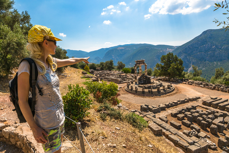 A young tourist dressed in sportswear pointing to the spectacular ruins of the Tholos at the sanctuary of Athena Pronaia seen from an overlook, Delphi, Archaeological Site, Central Greece. Stock Photo