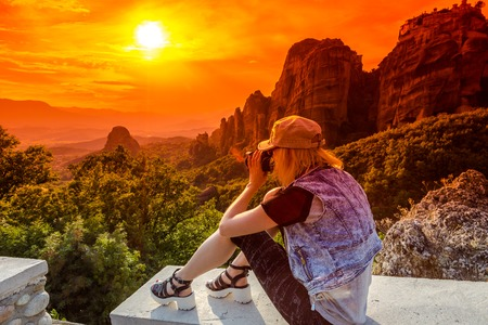 kalabaka: A travel photographer takes pictures of the spectacular monasteries of Meteora at sunset. Meteora is an area of Central Greece with several monasteries built on top of natural sandstone rock pillars. Stock Photo
