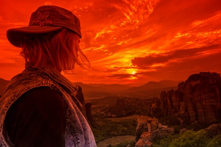 kalabaka: A tourist watching the spectacular scenery of the Monasteries of Meteora at sunset. Meteora is an area of Central Greece where several of monasteries are built on top of natural sandstone rock pillars