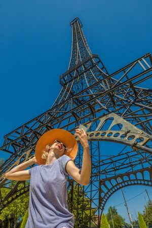 messenia: A smiling and fashionable woman with a orange wide-brimmed hat takes a selfie in front of Eiffel Tower sculpture in Filiatra Village, Peloponnese, Messenia, Greece.