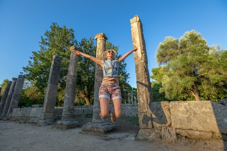 antigua grecia: A smiling and happy tourist jumps between the columns of the palaestra, where the athletes were training for the  Games. Ancient Olympia Archaeological Site, Peloponnese, Greece.