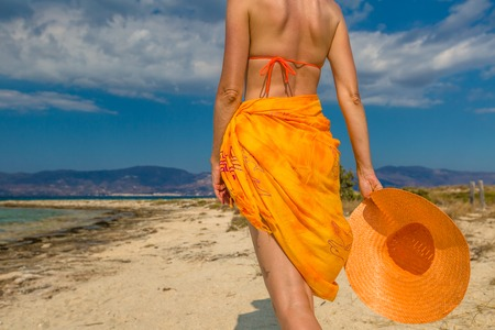 Beautiful woman, seen from behind, in orange walking in tropical beach. Elafonisos, the Greek version of the Maldives, the islands most exotic Mediterranean, Peloponnese, Greece.