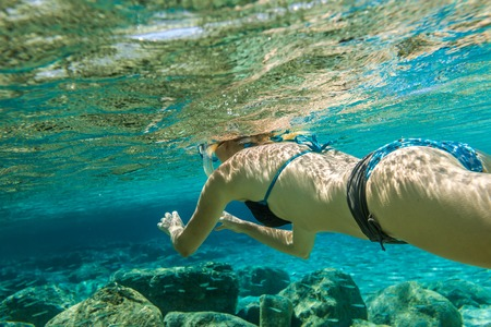 free diving: Woman free diving in beautiful turquoise waters of the famous Simos Beach, Elafonisos, Greek version of the Maldives, the islands most exotic Mediterranean, Peloponnese, Greece. Stock Photo