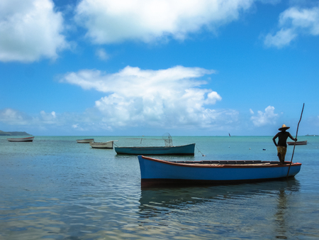 aux: Silhouette of a fisherman on a boat in the water, Ile aux Aigrettes Nature Reserve, Mauritius in the Indian Ocean.