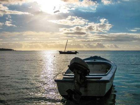 aux: Boat at sunset in the calm waters of the small port of Trou aux Biches, Mauritius, Indian Ocean, Africa. Stock Photo