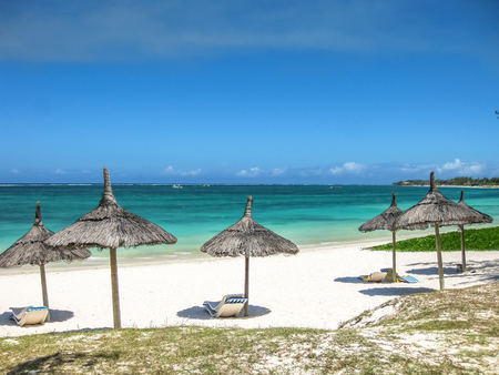 Thatch palapa umbrellas in the famous Belle Mare Beach, Mauritius, Indian Ocean, Africa.