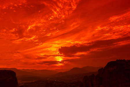 kalabaka: Famous lookout overlooking the city of Kalambaka at dramatic red sunset from the Monastery of the Holy Trinity, Meteora, Central Greece.