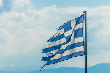 greek currency: Tattered Greek flag waving in the clouds on the blue sky background. concept for failure, debit, unique currency and financial bond