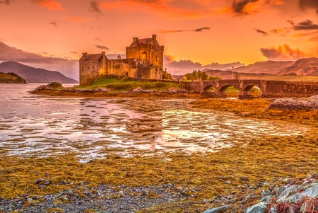 lochs: Eilean Donan Castle at sunset, Dornie, Kyle of Lochalsh in Scotland, United Kingdom. It is the most visited castle, situated on an island at the confluence of three sea lochs.