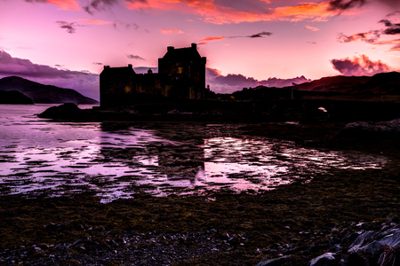 lochs: Eilean Donan Castle at evening, Dornie, Kyle of Lochalsh in Scotland, United Kingdom. It is the most visited castle, situated on an island at the confluence of three sea lochs.