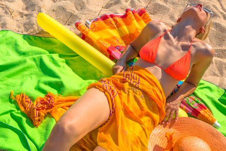float tube: A woman tanning lying on the beach with clothes and equipment by sea bright orange, green and yellow colors. Among the objects: sarong, hat, swimsuit, towel, beach umbrella and inflatable float tube.