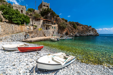greece: Boats on the shore in Alypa Beach, Mania Peninsula, Lakonia, Peloponnese, Greece, a beautiful stone beach with a transparent and turquoise sea.