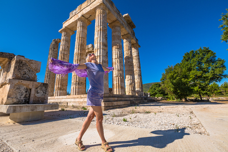 archaeological site: Smiling and fashionable woman dressed in violet color does fly his sarong in front of the ruins of the Temple of Zeus, Archaeological Site of Ancient Nemea, Peloponnese, Greece. Stock Photo