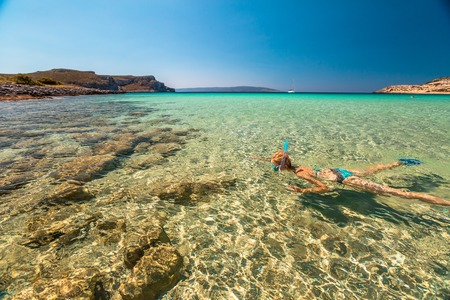 free dive: Woman snorkeling in beautiful blue waters of the famous Simos Beach, Elafonisos, Greek version of the Maldives, the most exotic island in Mediterranean , Peloponnese, Greece. Stock Photo