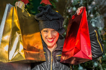 compras compulsivas: Retrato de una mujer feliz celebración de brillantes bolsas de compras para la Navidad.