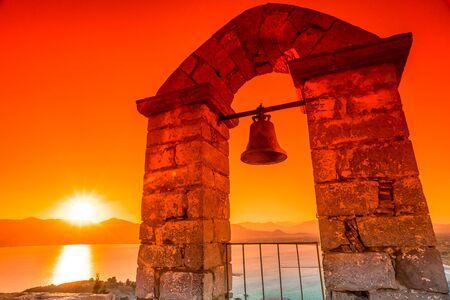 nafplio: Bell in a dramatic sunset sky in Palamidi  which dominates Nafplio city, Peloponnese, Greece.