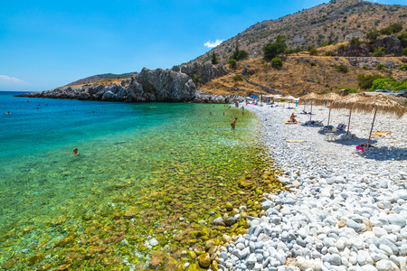 mania: Kokkala Beach, Mania Peninsula, Lakonia, Peloponnese, Greece - August 23, 2015: tourists swim and sunbathe on a beautiful stone Kokkala beach with a transparent and turquoise sea.