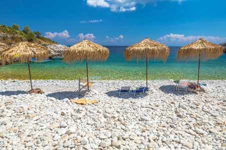 mania: Four palapa umbrellas in Kokkala Beach, Mania Peninsula, Lakonia, Peloponnese, Greece, a beautiful stone beach with a transparent and turquoise sea.