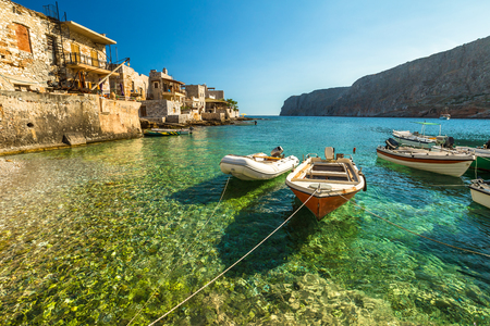 Fishing boats in the clear tropical waters of Gerolimenas, Mani Peninsula, Lakonia, Peloponnese, Greece.