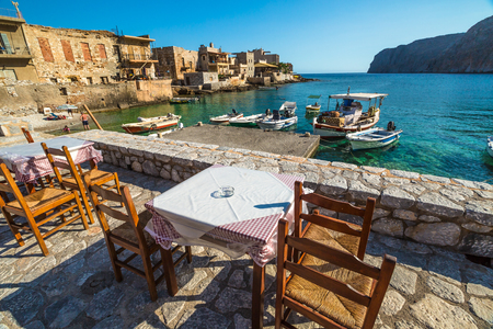 mania: Gerolimenas village, Mania Peninsula, Lakonia, Peloponnese, Greece - August 23, 2015: Typical tavern greek on waterfront between mountains and bay with tropical waters, pebble beach and fishing boats. Editorial
